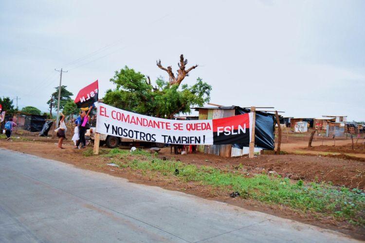 """Las mantas en apoyo al FSLN, que los tomatierras colocaron en el lugar invadido, aseguraban que el """"Comandante y ellos se quedan"""". LA PRENSA/ JADER FLORES"""