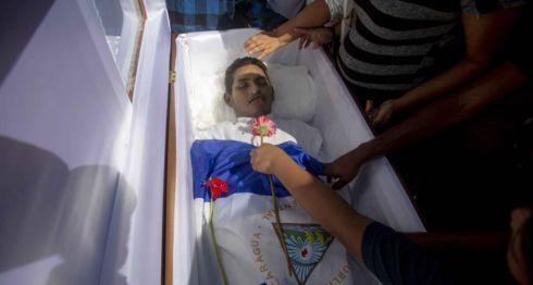 """Un joven pone una flor sobre el joven Ezequiel Gamaliel Leiva, de 26 años de edad, durante su entierro en el cementerio """"Milagro de Dios"""", a las afueras de Managua (Nicaragua) el pasado 18 de septiembre de 2018. LA PRENSA/ EFE"""