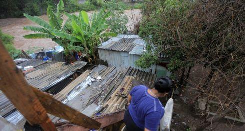 Una mujer recupera algunas de sus pertenencias tras una inundación provocada por el desbordamiento del río Choluteca en Tegucigalpa (Honduras). Las autoridades de Honduras declararon alerta roja en 3 departamentos del país, y la verde, de prevención, en los otros 15 por las fuertes lluvias. LA PRENSA/ EFE/Gustavo Amador