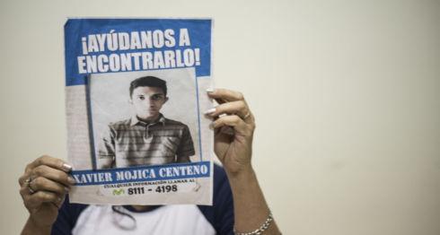 La madre de Xavier Mojica, Lorena Centeno, se tapa el rostro con el cartel de su hijo. LA PRENSA/O. Navarrete