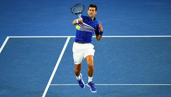 El tenista serbio Novak Djokovic golpea la bola contra el francés Lucas Pouille durante la semifinal masculina del Abierto de Australia que disputaron este viernes en Melbourne, Australia. LA PRENSA/EFE/ Julian Smith