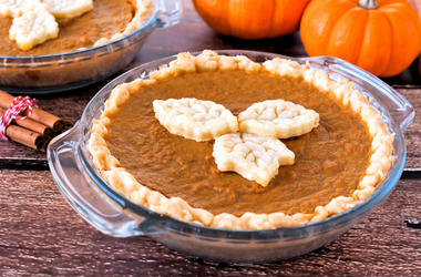 Thanksgiving pumpkin pie with leaf pastry toppings against a rustic wood background