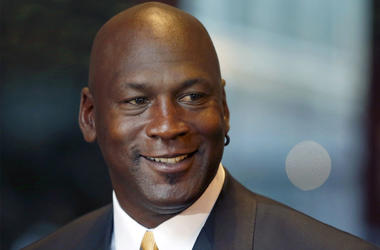 In this Aug. 21, 2015, file photo, former NBA star and current owner of the Charlotte Hornets, Michael Jordan smiles at reporters in Chicago. A quarter century after being famously excluded from the cult favorite video game NBA Jam, Jordan is investing in