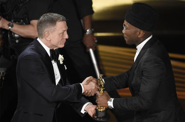 """Daniel Craig, left, presents Mahershala Ali with the award for best performance by an actor in a supporting role for """"Green Book"""" at the Oscars on Sunday, Feb. 24, 2019, at the Dolby Theatre in Los Angeles. (Photo by Chris Pizzello/Invision/AP)"""