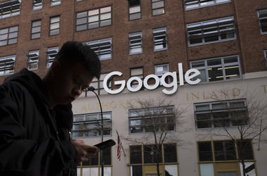 In this Dec. 17, 2018, file photo a man using a mobile phone walks past Google offices in New York. (AP Photo/Mark Lennihan, File)