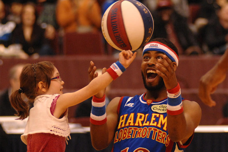 """Harlem Globetrotters' player Ant entertains a girl during their 2014 """"Fans Rule"""" World Tour basketball show on Feb.13, 2014 in Vancouver, Canada. The Harlem Globetrotters are an exhibition basketball team that combines athleticism, theater and comedy. Ove"""