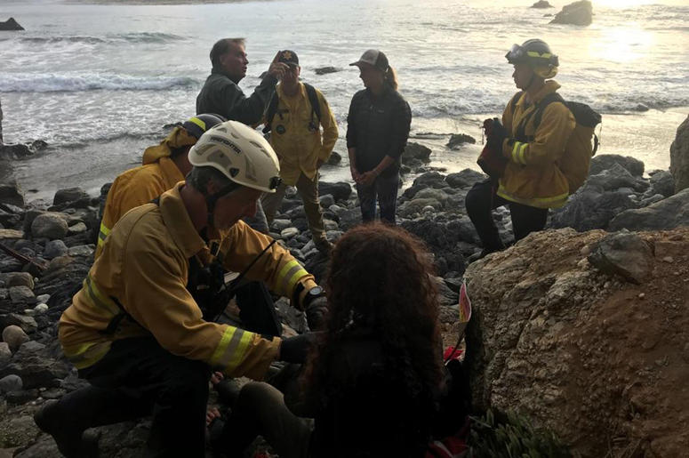 In this Friday, July 13, 2018, photo posted on the Monterey County, Calif., Sheriff's Office Twitter feed, authorities tend to Angela Hernandez, foreground center, after she was rescued, in Morro Bay, Calif. Authorities say a couple on a camping trip came