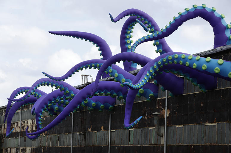 "An inflatable sculpture entitled ""Sea Monsters HERE"" extends from a rusting warehouse called Building 61 at the Navy Yard in Philadelphia, Tuesday, Oct. 9, 2018. The installation was created by UK-based artists Filthy Luker and Pedro Estrellas. The former"