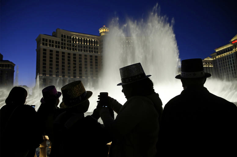 In this Dec. 31, 2015, file photo, people watch the fountains at the Bellagio while wearing paper hats to celebrate New Years Eve in Las Vegas. Las Vegas will usher in 2019 trying to outdo itself with performances by Lady Gaga, Gwen Stefani, Bruno Mars an