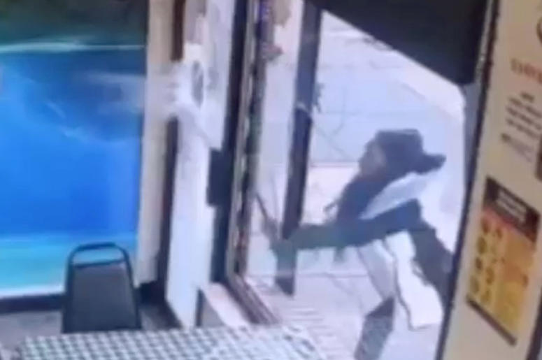 """In this Jan. 15, 2019 image taken from surveillance video, a woman smashes the windows of """"Back Home Restaurant"""" in the Bronx borough of New York. Police say that she became upset after ordering a patty and was told that the restaurant had run out of them"""