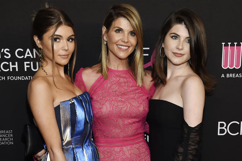 """In this Feb. 28, 2019 file photo, actress Lori Loughlin, center, poses with daughters Olivia Jade Giannulli, left, and Isabella Rose Giannulli at the 2019 """"An Unforgettable Evening"""" in Beverly Hills, California. (Photo by Chris Pizzello/Invision/AP, File)"""