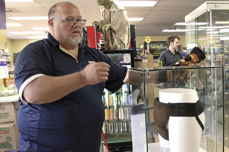 """In this May 2, 2018 file photo, Blockbuster Alaska general manager Kevin Daymude moves a display case featuring the jockstrap worn by actor Russell Crowe in the 2005 movie """"Cinderella Man"""" at a Blockbuster video store in Anchorage, Alaska. Everything in t"""