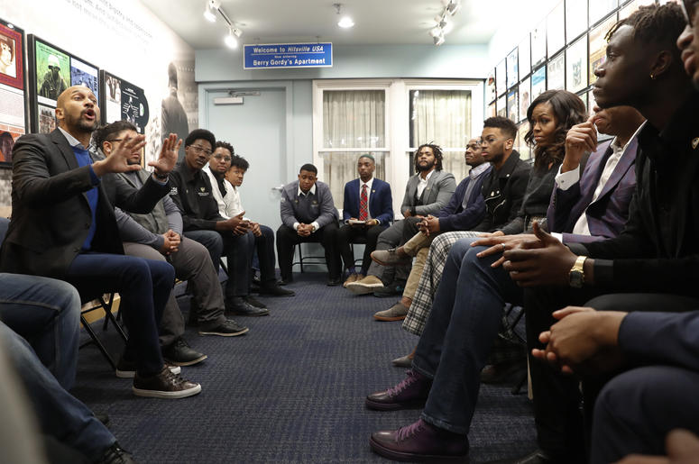 Actor Keegan-Michael Key, left, speaks while former First Lady Michelle Obama, right, listens with Wayne State University students at the Motown Museum in Detroit, Tuesday, Dec. 11, 2018. (AP Photo/Paul Sancya)
