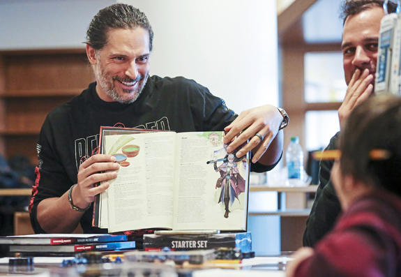 Actor and Mt. Lebanon, Pa. native Joe Manganiello, left, reads the Dungeons and Dragons character options to brother Nick Manganiello, top right, and UPMC Children's Hospital patient and first time D&D player Gabriel Bowers, 9, of Shaler, Pa., right, at U
