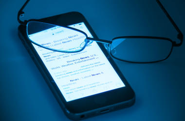 Glasses laying on cell phone with News on screen