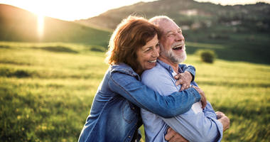 older couple embracing on an outdoor hike
