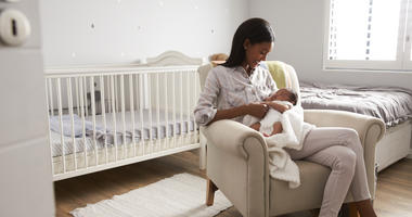 new mother holding baby in baby room