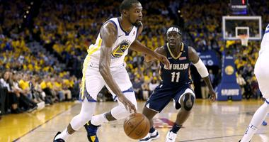 Apr 28, 2018; Oakland, CA, USA; Golden State Warriors forward Kevin Durant (35) dribbles past New Orleans Pelicans guard Jrue Holiday (11) in the third quarter in game one of the second round of the 2018 NBA Playoffs at Oracle Arena.