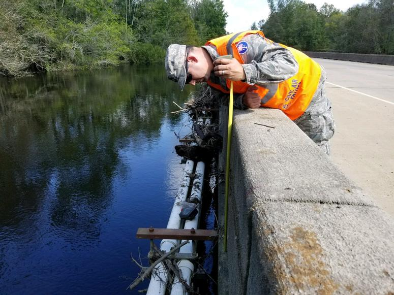 Lt. Col. George Stanley takes a high water mark measurement on the Senator Roger W. Scott Memorial Bridge