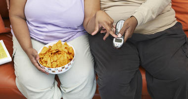 Fat people eating on a couch - obesity