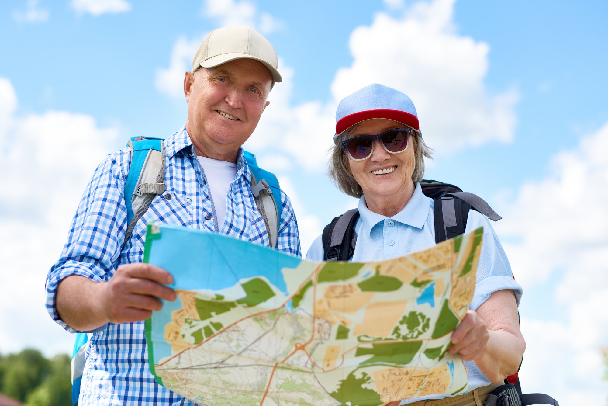Happy Senior Tourists Holding Map