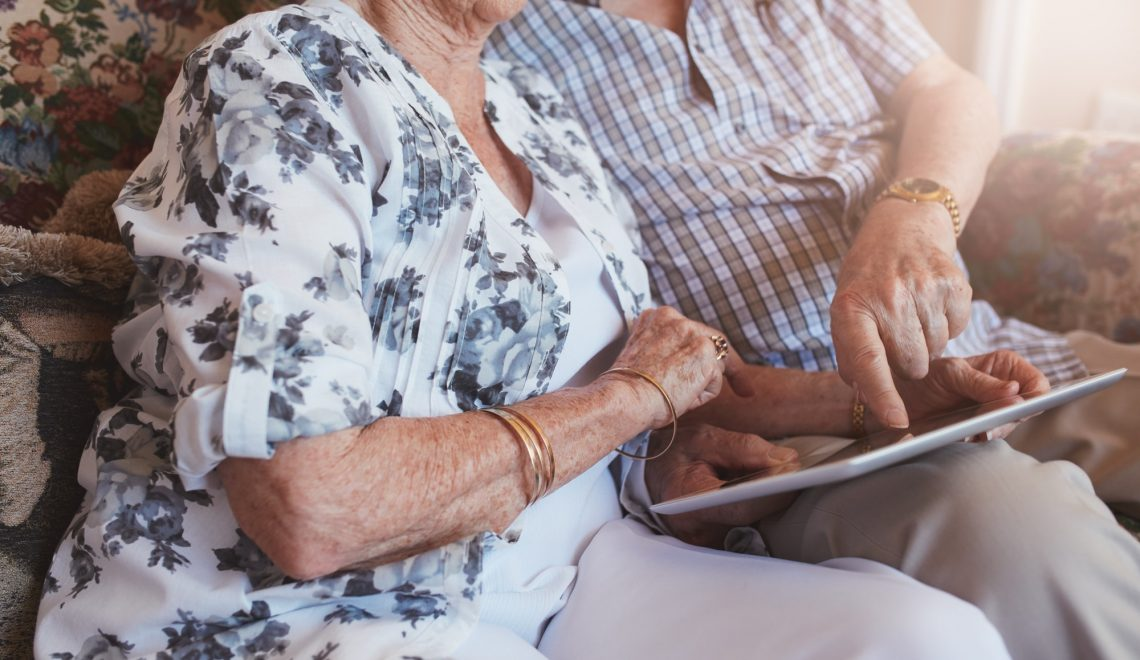 Senior couple sitting together using touch screen computer