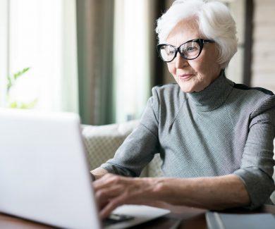 Senior woman typing on laptop