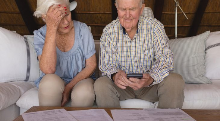 Worried senior couple discussing over medical bills at home