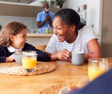 Grandparents Sitting In Kitchen With Grandchildren Eating Breakfast Before Going To School