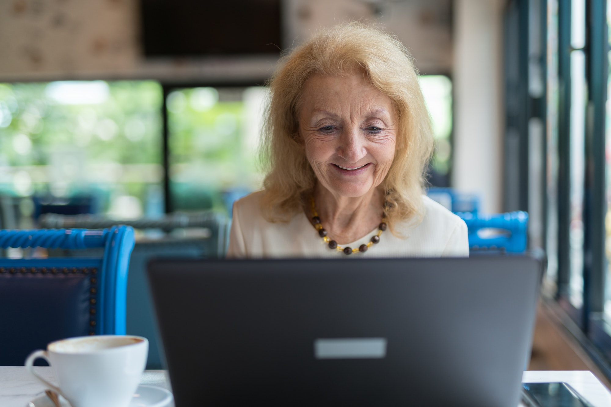 Happy senior woman smiling and using laptop computer in coffee shop