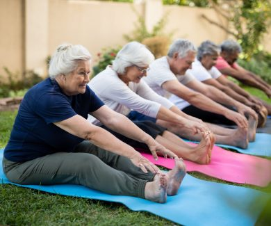 Cheerful seniors exercising on mats at park