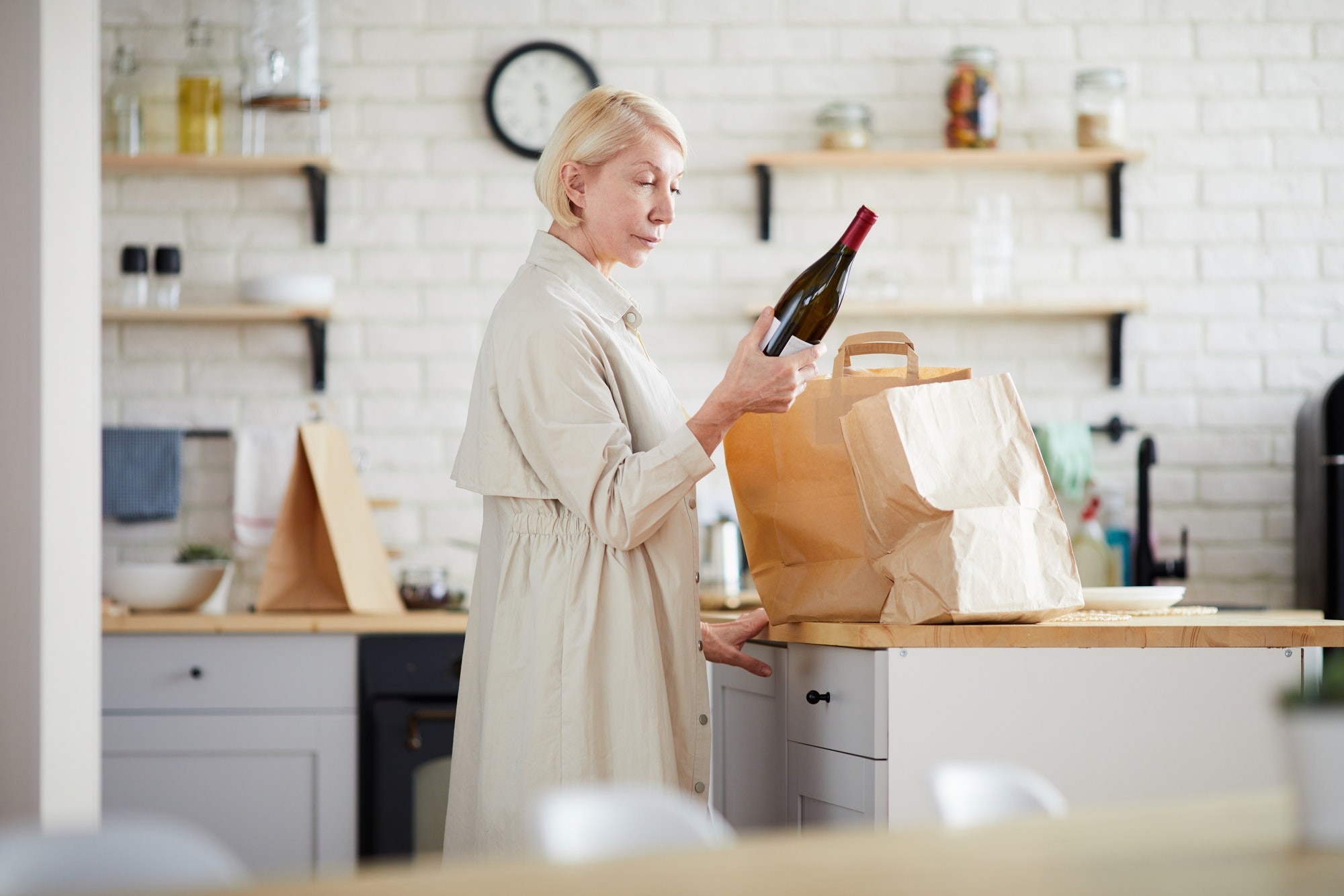 Mature lady unpacking paper bags in kitchen