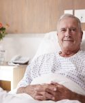 Portrait Of Male Senior Patient Lying In Hospital Bed Smiling At Camera