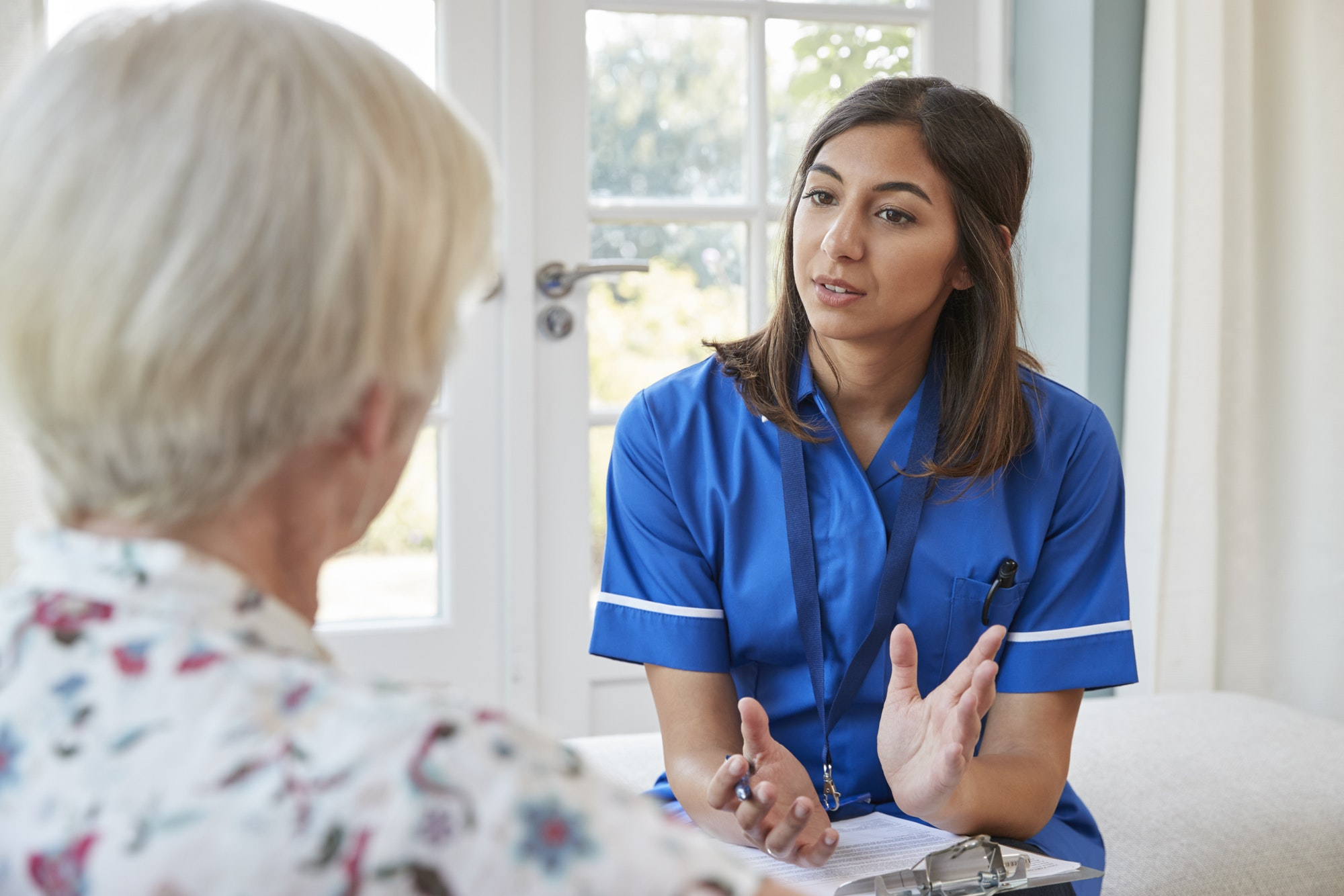 Senior woman talking to young care nurse on home visit