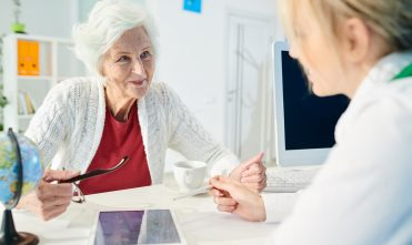 Smiling senior lady choosing travel tour with manager