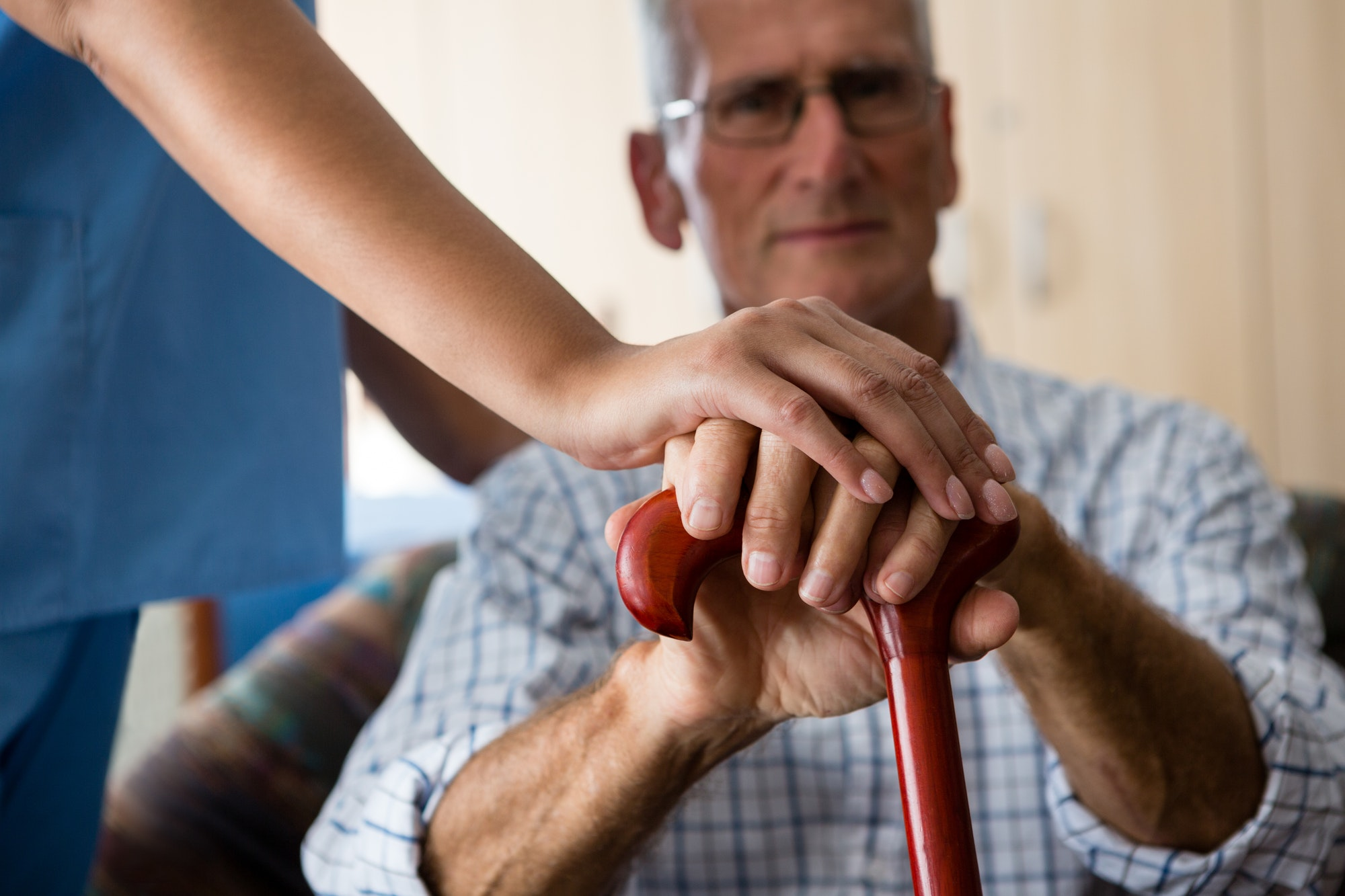 Close up of female doctor and senior man hands holding walking cane