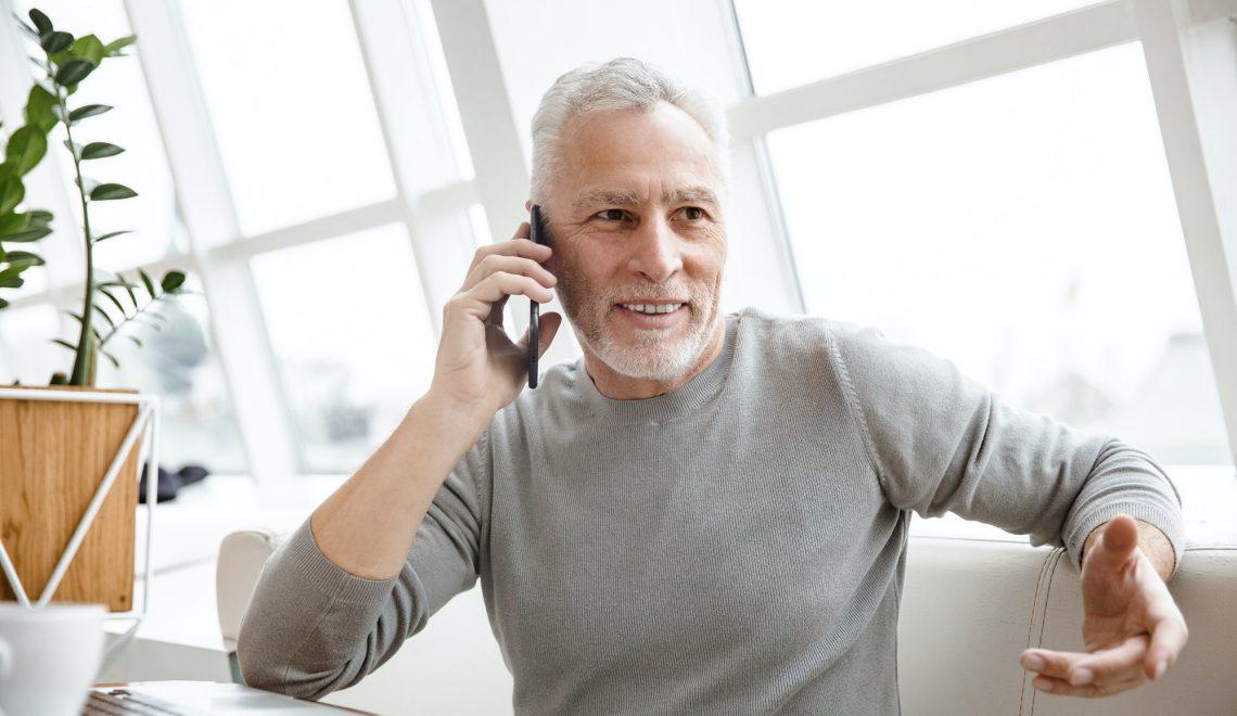 Mature senior businessman talking by mobile phone.
