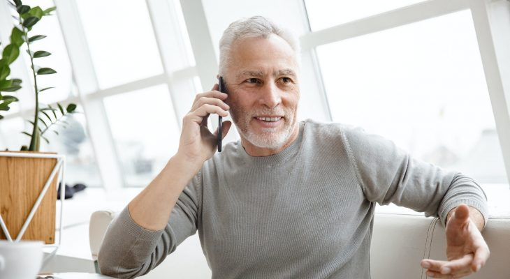 Mature senior businessman talking by mobile phone.