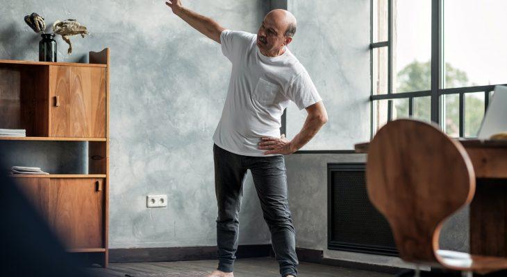 Senior man practicing yoga trikonasana pose at the living room