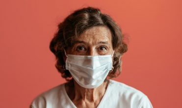 Senior woman against pink background looking straight at camera wearing face mask.