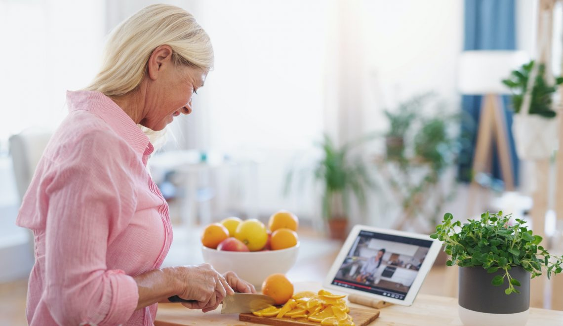 Senior woman preparing food in kitchen indoors, following food vlogger