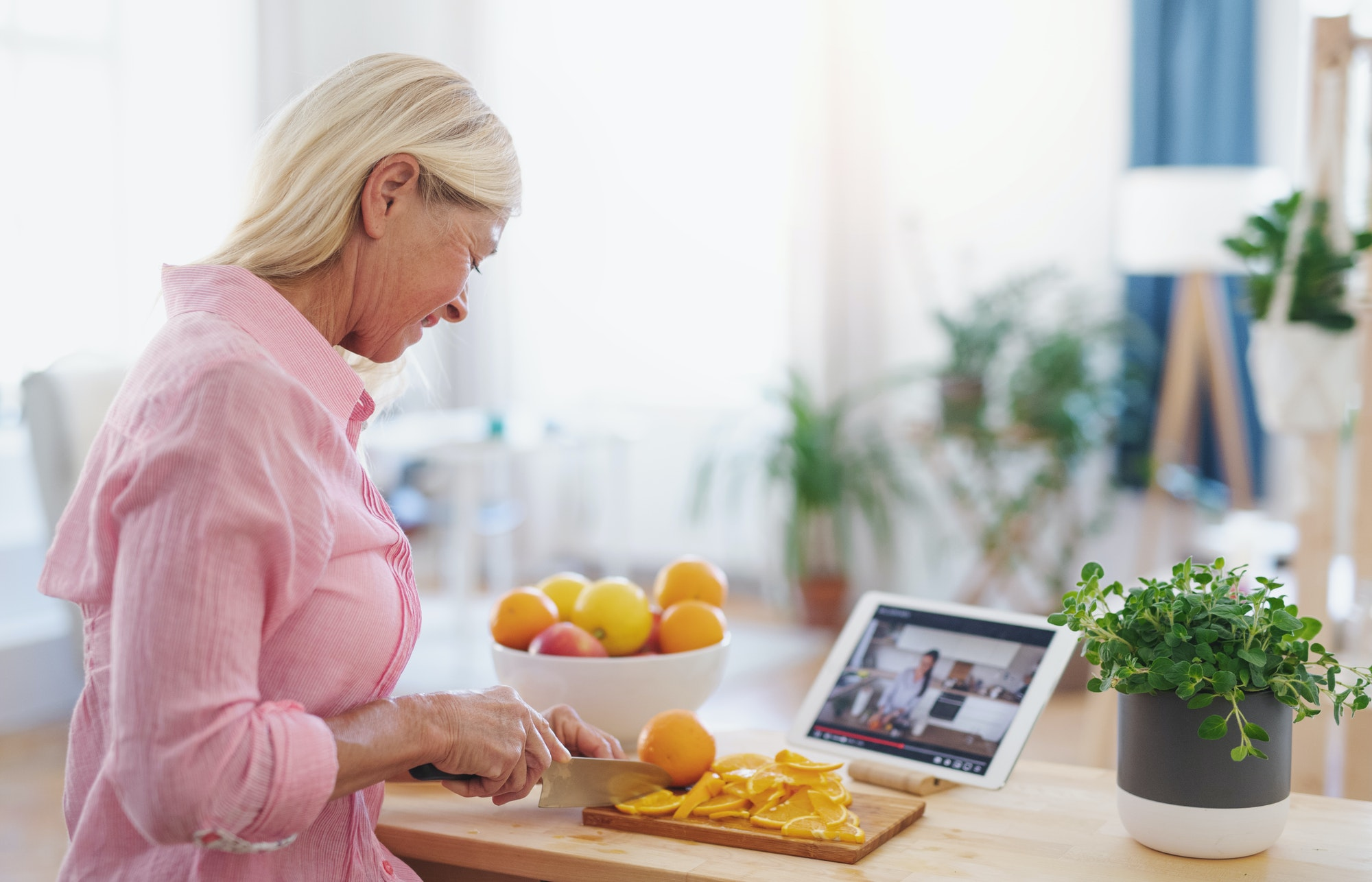 Senior woman preparing food in kitchen indoors, following food vlogger