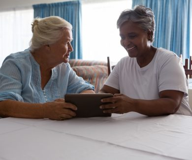 Senior woman showing digital tablet to friend at table