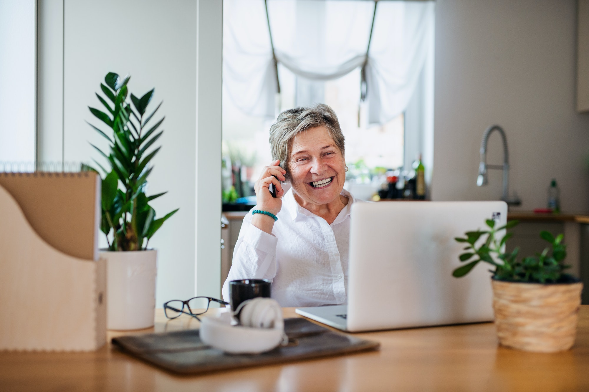 Senior woman with laptop and smartphone working in home office