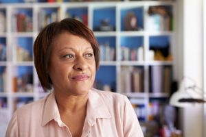 Smiling Mature Woman In Home Office By Bookcase