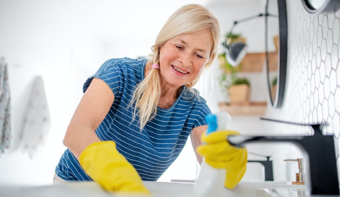 Senior woman with gloves cleaning bathroom indoors at home