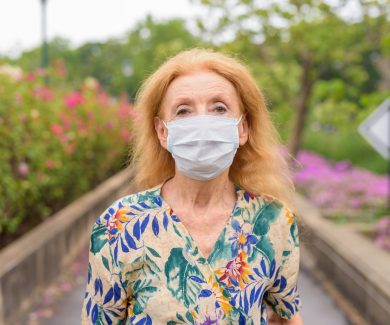 Face of blonde senior woman wearing mask for protection from corona virus outbreak at the park