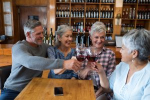 Group of smiling senior friends toasting glass of wine