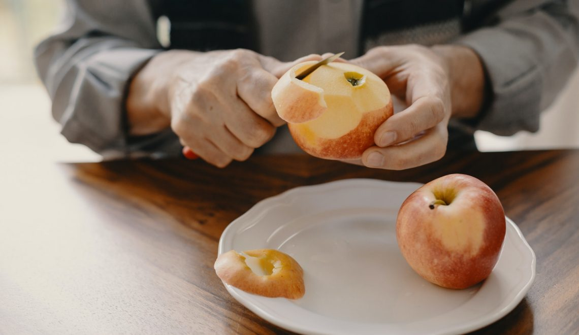 Senior caucasian man peeling an apple with a knife sitting at the wooden table