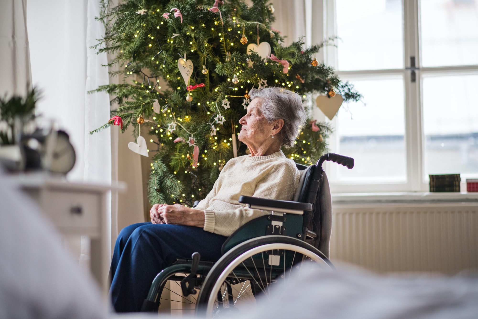 A senior woman in wheelchair at home at Christmas time.